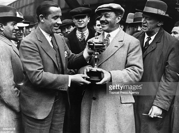 Golfer Walter Hagen hands J H Batley Chairman of the Golfers Association the Ryder Cup on arrival at Paddington London Hagen is one of 17 American...