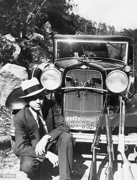 Portrait of American outlaw Clyde Barrow crouching in front of a car with a handgun hanging from the hood ornament, two handguns in the front grill...