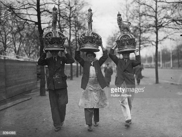Three workmen carry huge crowns on their heads ready to place in position in The Mall London as part of the decorations celebrating George V's Silver...
