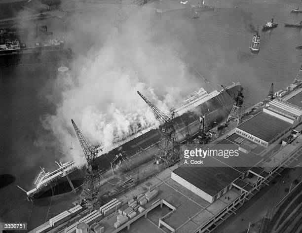 The French Liner 'Paris' on its side and on fire at Le Havre docks