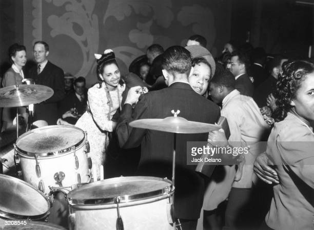 AfricanAmerican couples dance to the music of 'Red' Sounders and his band at the Club Delisa Chicago Illinois