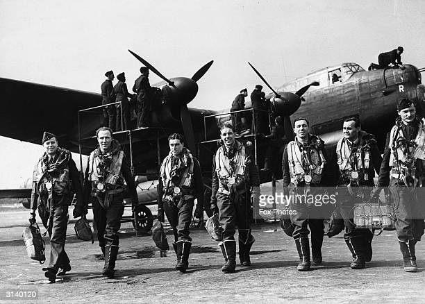The crew of a Lancaster bomber walk away from their plane after a flight while ground crew check it over