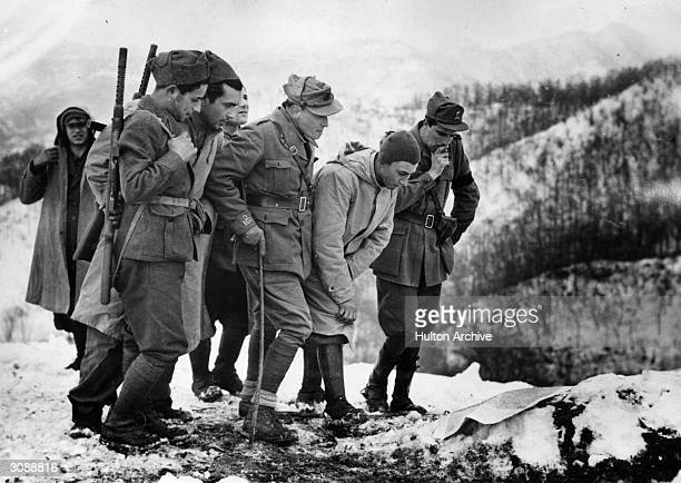 Group of Italian soldiers study a map spread on a snow-covered dugout near a front line mountain peak in Italy. This advanced Italian post is...
