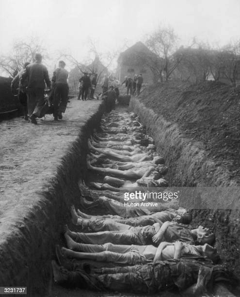 Allied soldiers remove emaciated corpses from a mass grave at the Nordhausen concentration camp a subcamp of the concentration camp DoraMittelbau in...