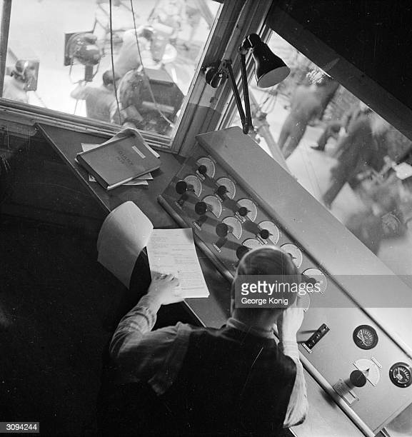 Technician at the BBC television station at Alexandra Palace, London watches the cameras in the studio below and alters the images using the...