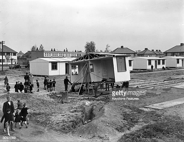 Schoolchildren helping the workmen construct a new estate of prefabricated houses in Watford Hertfordshire after the devastation of World War II
