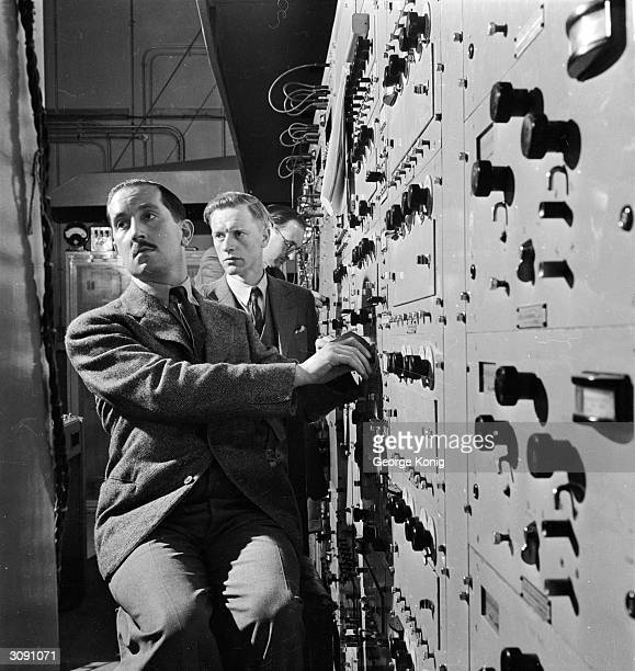 Two technicians manning the banks of equipment in the vision control room of the BBC television station at Alexandra Palace London The man in the...