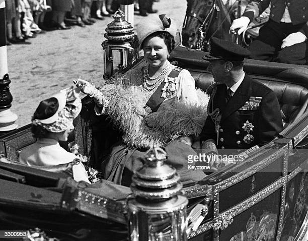King George VI and Queen Elizabeth with their daughter Princess Margaret Rose in an open carriage forming part of a procession to St Paul's Cathedral...