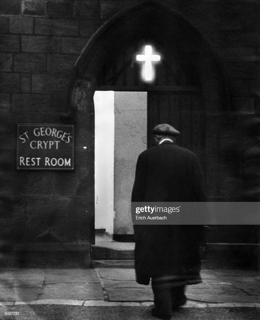 An elderly man enters St George's crypt in Leeds where he will be warm, can get a meal and maybe sleep the night. The cross above the door is illuminated all through the night.