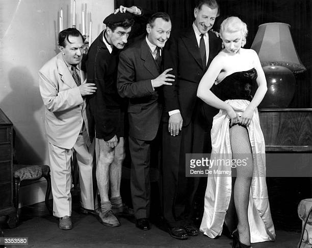 A publicity still of Richard Murdoch and fellow actors in a scene from 'As Long as They're Happy' at the Grand Blackpool Murdoch and a line of men...