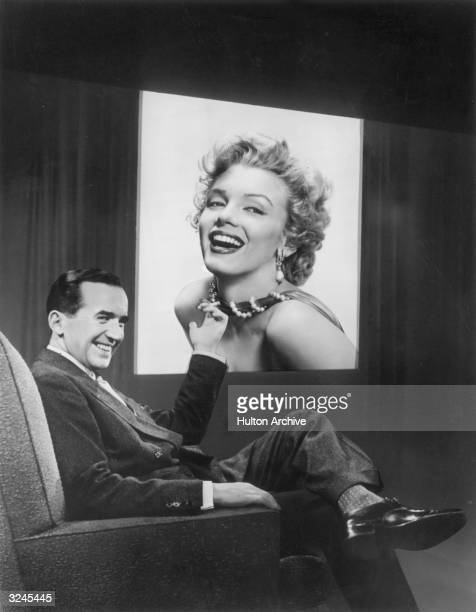 American broadcast journalist Edward R Murrow points to an image of actor Marilyn Monroe subject of a forthcoming television interview on 'Person to...