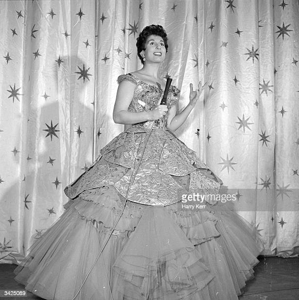 English singer Alma Cogan on stage wearing a large dress