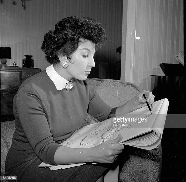 English singer Alma Cogan sketching a design for a new dress