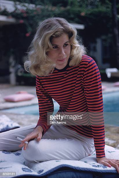 Nonni Phipps wearing a striped top as she poses by her swimming pool in Palm Beach Florida