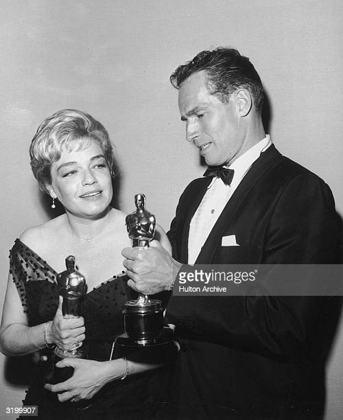 American actor Charlton Heston and Germanborn actor Simone Signoret talk as hold their Oscars at the Academy Awards Los Angeles California Heston won...