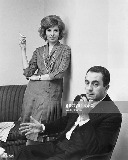 Italian film director Michelangelo Antonioni sits in a chair looking at the camera as Italian actor Monica Vitti leans against the wall behind him...