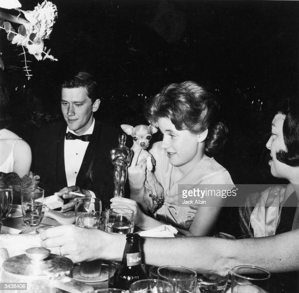 American actor Patty Duke holds her Oscar statuette and her pet chihuahua Bambi while seated next to Andy Prine during the Academy Awards party held...