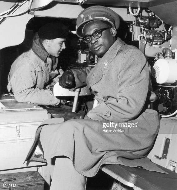 General Joseph Mobutu Chief Commander of the National Congolese Army examines the interior of an armored car during a tour of a military infantry...
