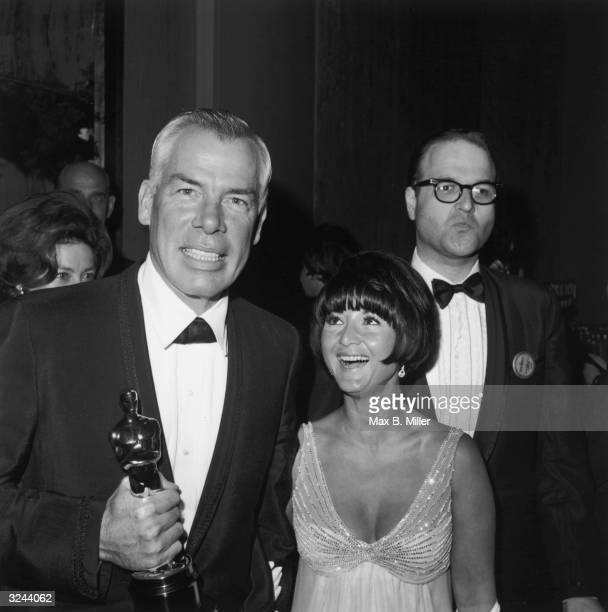 American actor Lee Marvin wearing a tuxedo smiles while holding an Oscar statuette next to Michelle Triola who laughs while facing him at the Academy...