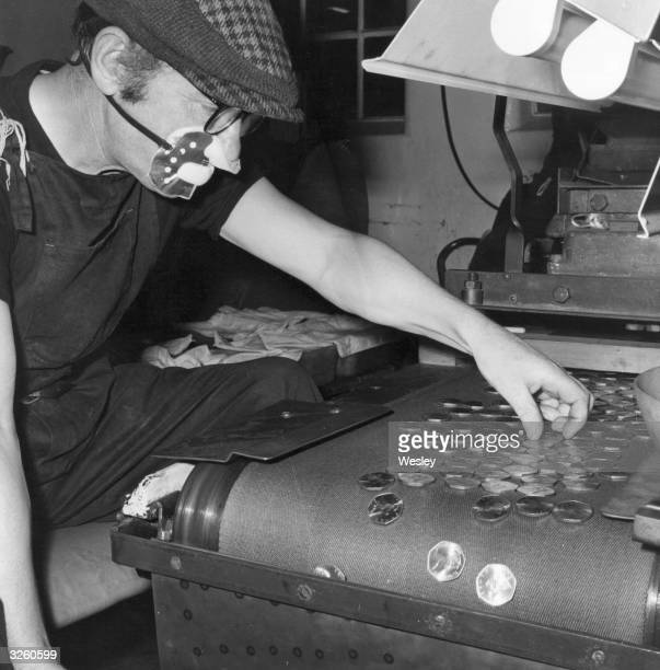 Employee Patrick Rogers makes a final check of the new fifty pence coins at the Royal Mint in advance of Britain's conversion to decimalisation