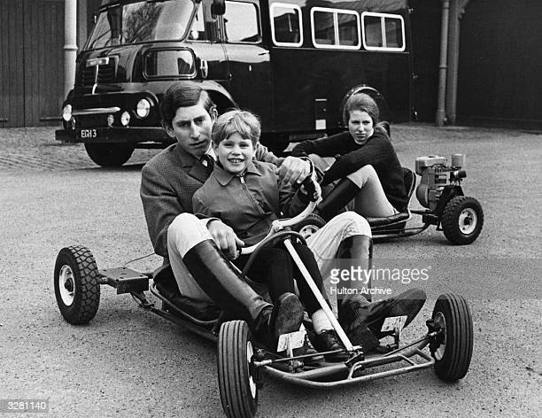 Charles Prince of Wales and Prince Edward riding together in gokart whilst Princess Anne drives behind them
