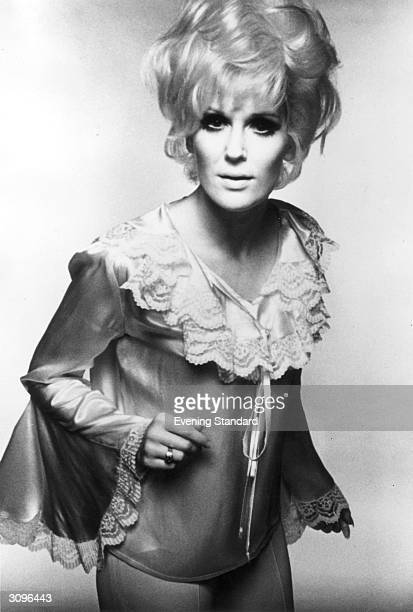 English pop singer Dusty Springfield wearing a frilly satin top.