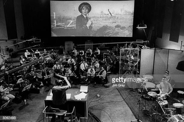 Malcolm Arnold conducts a 70piece orchestra as they record music onto the film track for 'The Battle of Britain' The score by Sir William Walton was...