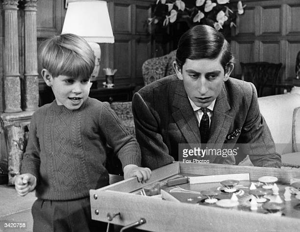 Prince Charles looks on as his five year old brother Prince Edward enjoys a game of bagatelle at Sandringham House, Norfolk.