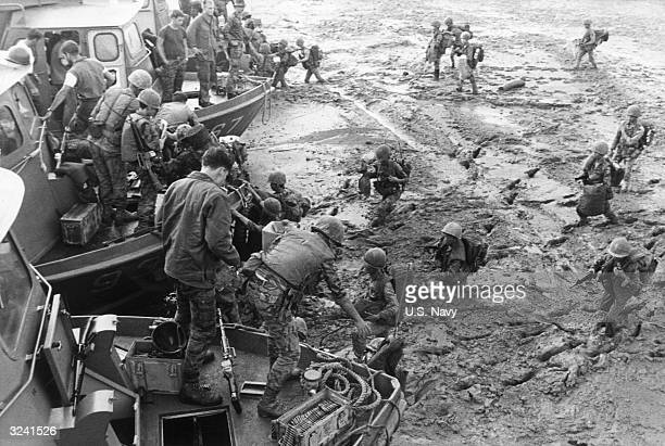 Vietnamese troops wade through thick, waist-high mud to board US Navy inshore patrol crafts on the Song Cau Lon River, following a sweep near old Cam...