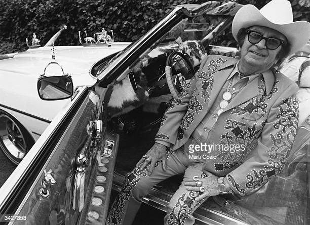 Nudie Cohen known as Nudie Russianborn costume designer for many country and western singers sitting in his famous white Pontiac convertible The car...