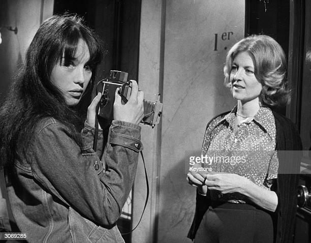 French actress Isabelle Adjani takes a photograph of Nicole Courcel between takes of Claude Pinoteau's film 'La Gifle' at the Billancourt Studios
