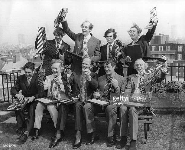 The Top Ten Tiemen celebrate their victory by displaying their winning ties at a presentation at the Playboy Club Park Lane Standing left to right...