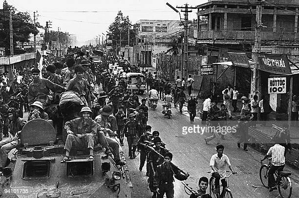 A 30 April 1975 photo shows jubilant communist troops on top of trucks and APCs making their way to the centre of Saigon as the city fell under their...