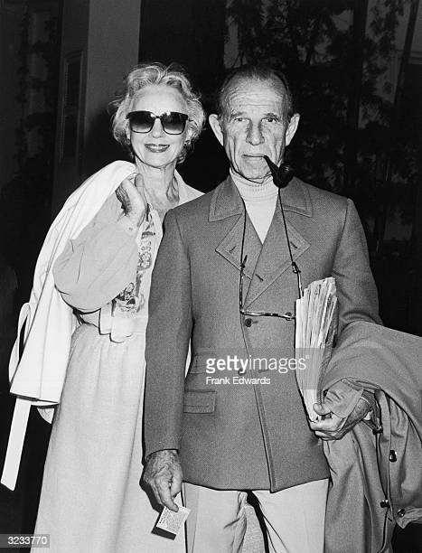 British actor Jessica Tandy stands behind her husband Canadian actor Hume Cronyn who wears sunglasses while he smokes a pipe between his teeth at an...