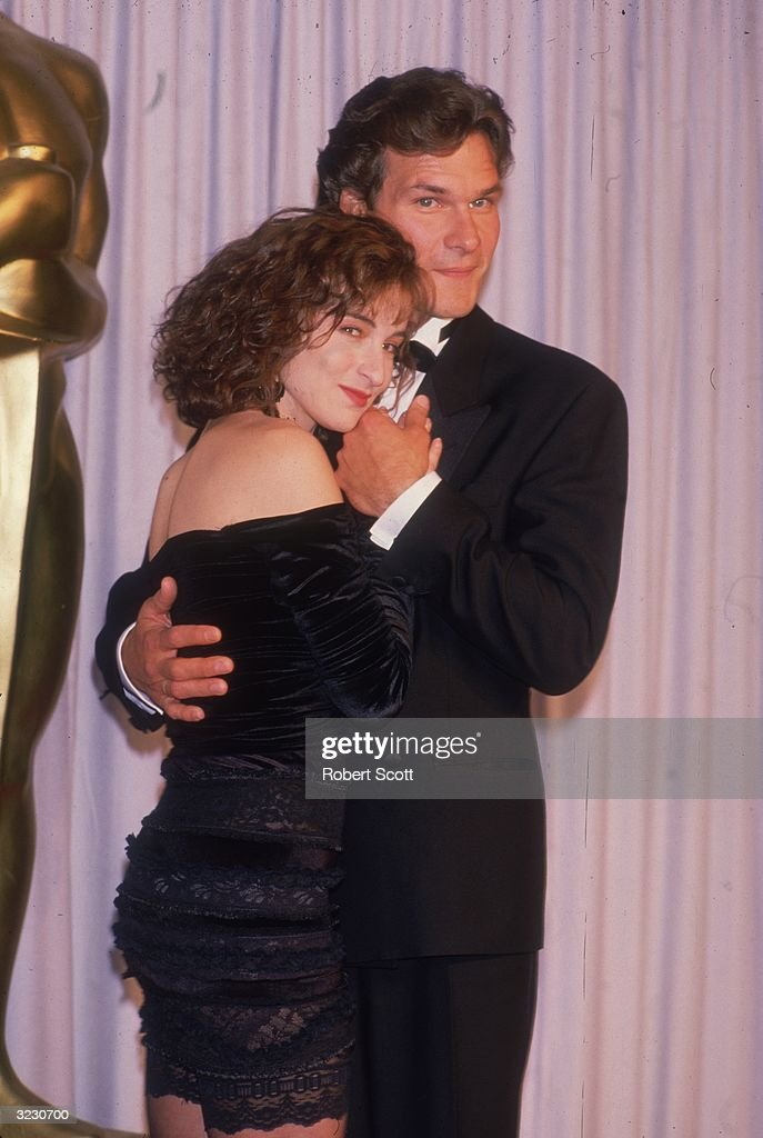 American actors Patrick Swayze and Jennifer Grey, costars of director Emile Ardolino's film 'Dirty Dancing,' embrace in front of a curtain at the Academy Awards, Los Angeles, California.