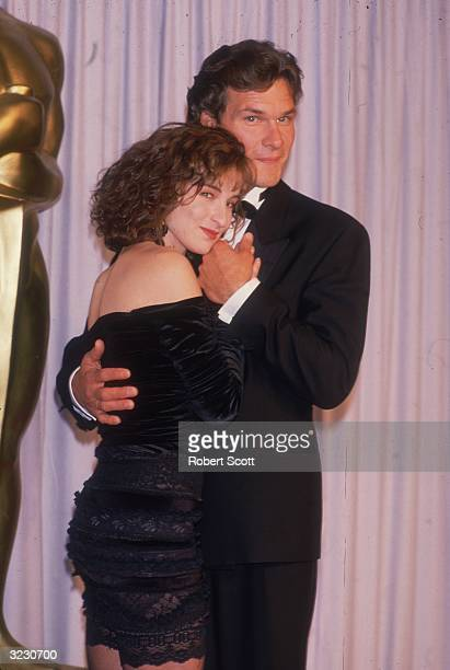 American actors Patrick Swayze and Jennifer Grey, costars of director Emile Ardolino's film 'Dirty Dancing,' embrace in front of a curtain at the...