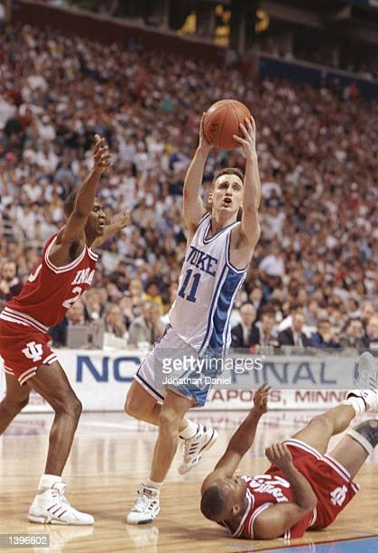 Guard Bobby Hurley of the Duke Blue Devils drives between guard Greg Graham and Damon Bailey of the Indiana Hoosiers during a playoff game at the...