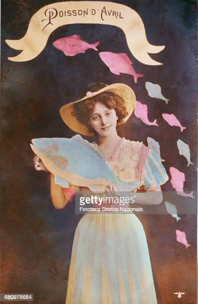 girl smiles encircled from a flock of fishes of April on paper and in hand she keeps one more large Postcard photograph handcolored France approx 1915