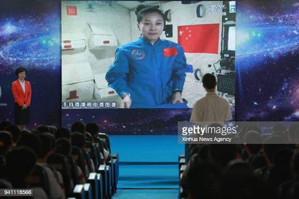 A student asks questions to female astronaut Wang Yaping who is aboard Tiangong1 space lab module at the High School Affiliated to Renmin University...