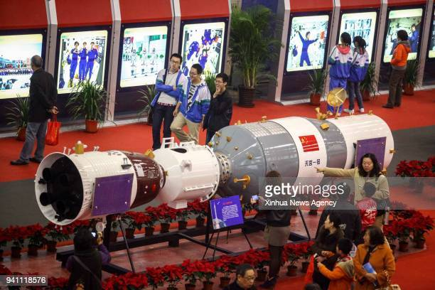 People look at a model of the Shenzhou10 manned spacecraft docked with Tiangong1 space lab module during an exhibition in Tianjin north China Nov 9...