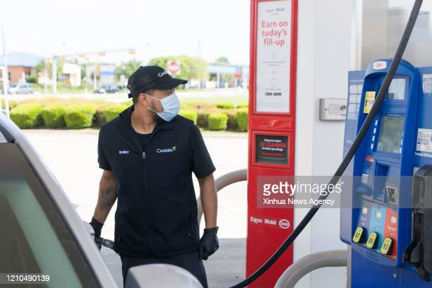 S April 20 2020 A man wearing a face mask fills up in Plano Texas the United States on April 20 2020 US oil prices crashed to the negative territory...