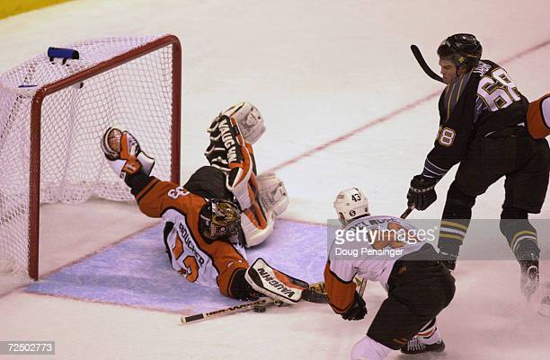 Brian Boucher goaltender for the Philadelphia Flyers makes a save on a shot by Jaromir Jagr of the Pittsburgh Penguins as Andy Delmore of the Flyers...