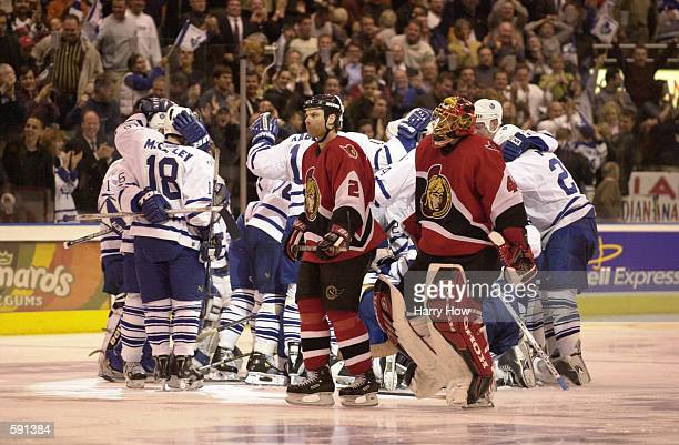 Curtis Leschyshyn and Patrick Lalime of the Ottawa Senators skate past the celebrating Toronto Maple Leafs after game 3 of the eastern conference...