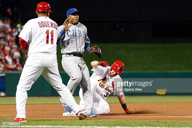 Chicago Cubs third baseman Luis Valbuena waits for the ball as St. Louis Cardinals first baseman Matt Adams steals third base on a passed ball during...