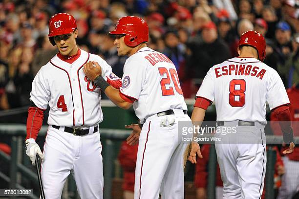 Washington Nationals shortstop Ian Desmond and second baseman Danny Espinosa are congratulated by shortstop Zach Walters after scoring on a wild...