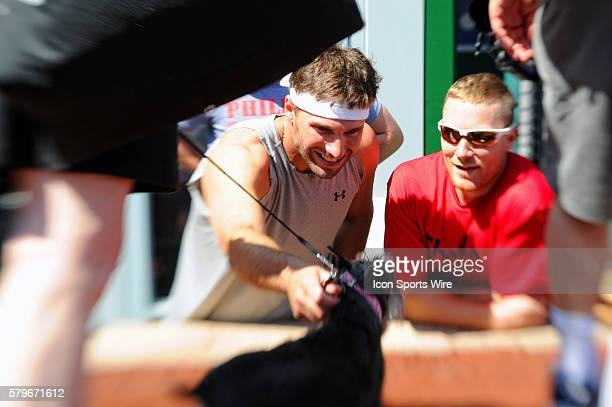 Philadelphia Phillies right fielder Jeff Francoeur and third baseman Cody Asche reach to pet a dog during the
