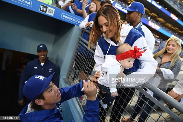 Los Angeles Dodgers Starting pitcher Kenta Maeda [1797] signs the sweatshirt of 3 month old Taydem Mendez as mother Kacy Mendez carefully holds her...