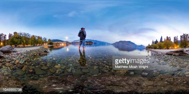 april 2017, queenstown, new zealand. a 360 view of a man as he wades out into the water of the beautiful scenic lake wakatipu at sunset. - 全天周パノラマ ストックフォトと画像