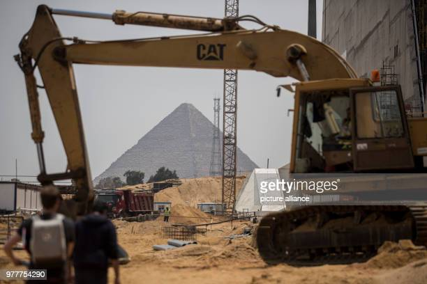 A construction machine is on the grounds of the Grand Egyptian Museum the Great Pyramid of Giza can be seen in the background The museum close to the...