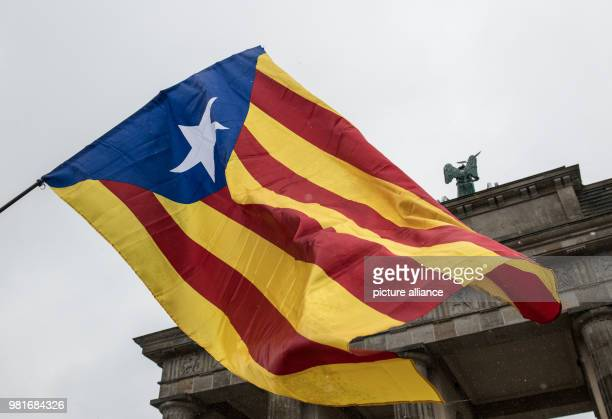 A Catalonian flag waving in the wind at a demonstration for an independent Catalonia at the Brandenburg Gate The citizens' initiative Assemblea...